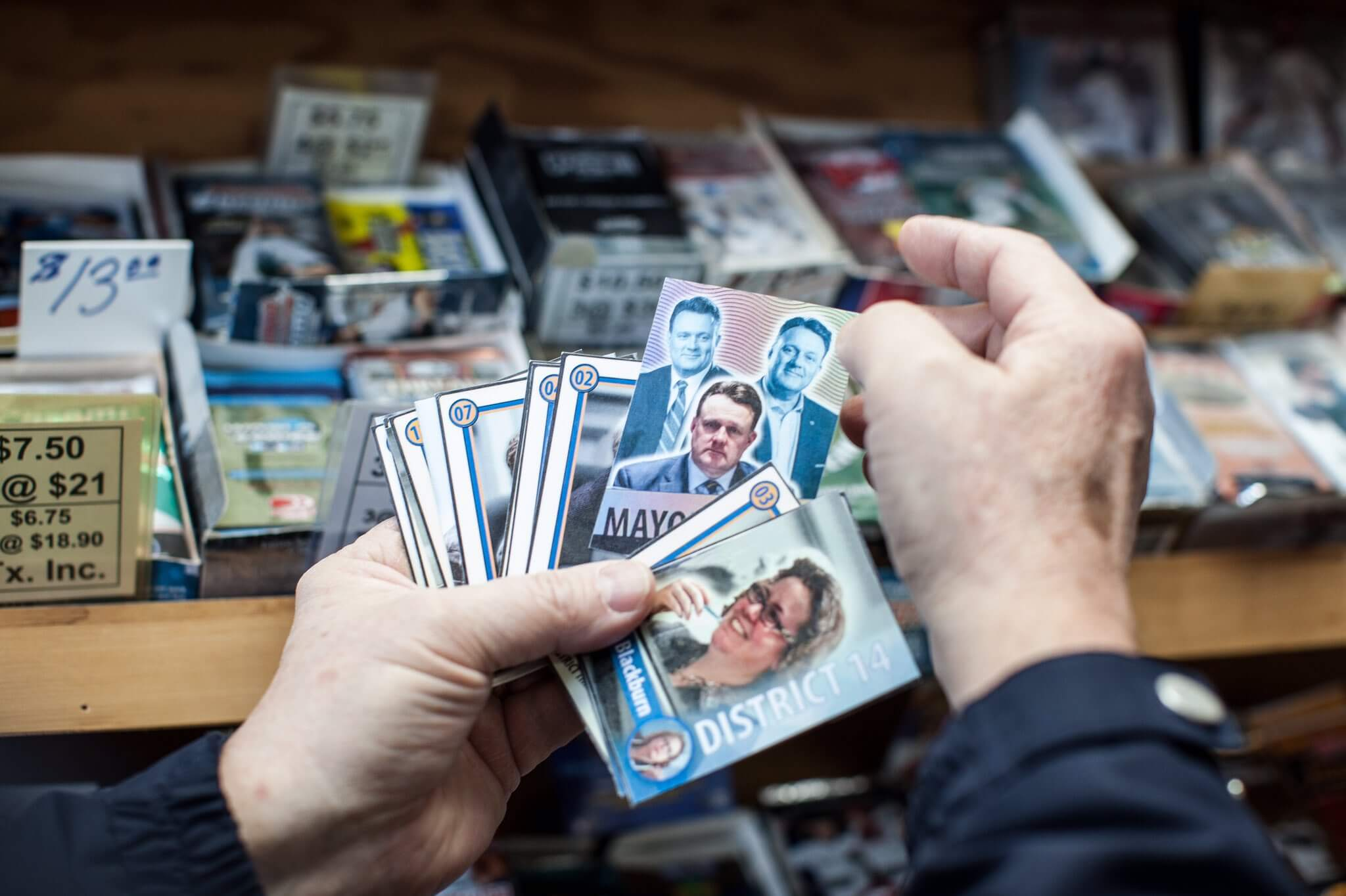 product photography of hands holding a set of printed parody hockey card designs with politicians